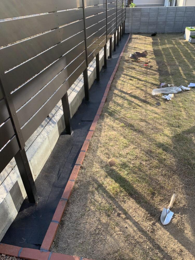 塀の近くの防草シートの画像